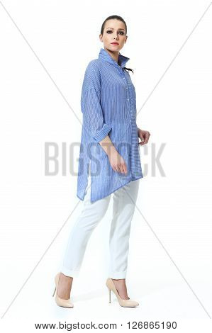 eastern woman with straight pony tail hair style in baggy blue casual shirt and trousers high heel shoes going full body length isolated on white
