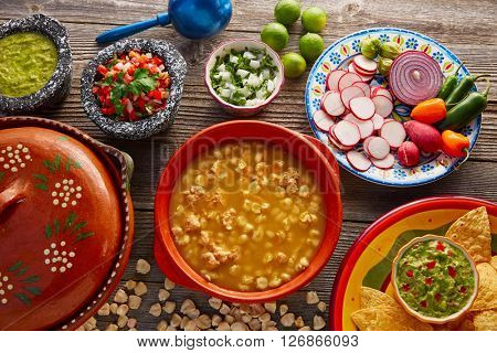 Green Pozole verde with blanco mote corn and ingredients on wooden table