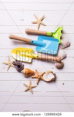 Vacation concept.Tools for kids for playing in sand and sea objects on white painted wooden planks.