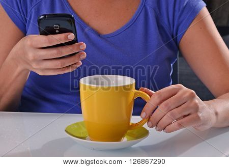 Drinking coffee and using cell phone. Chatting coffee break.