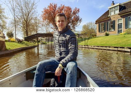Tourist in a rented boat is taking a tour through Giethoorn village in the Netherlands