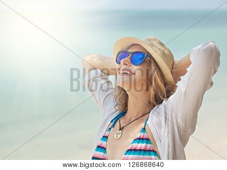 Beautiful Young Woman In A Hat And Sunglasses On The Background Of Sea And Sun. Beach Vacation, Holi