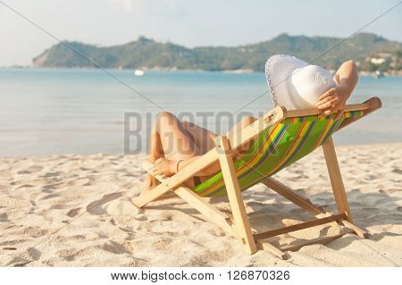 Woman In A Hat On A Beach, Sitting In A Deck Chair And Watching The Sea