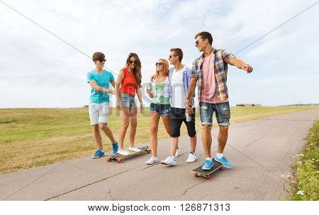 people, leisure and sport concept - group of happy teenage friends with longboards and drinks outdoors