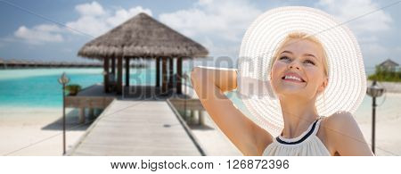 people, summer holidays, travel, tourism and vacation concept - beautiful woman in sun hat enjoying summer over maldives beach with bungalow background