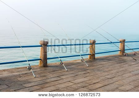 Five fishing rods leaning on blue handrail with foggy ocean background