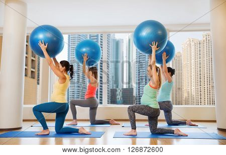 pregnancy, sport, fitness, people and healthy lifestyle concept - group of happy pregnant women exercising with ball in gym over city window view background
