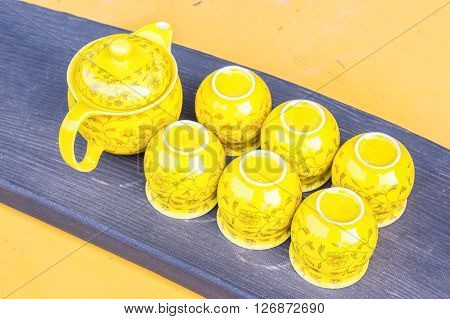 Six Chinese yellow tea cups and a tea pot with floral design on a black wood outside