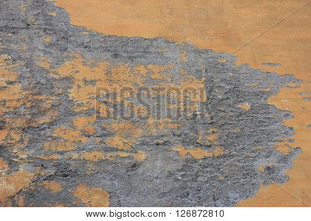 dilapidated crumbled medieval plastered orange wall in small roman street