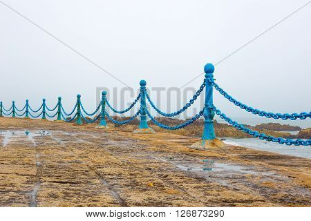 Blue metal pillars witch chains protection against falling into the ocean on foggy day