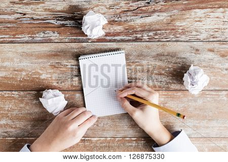 business, education, inspiration and people concept - close up of female hands with notebook, pencil and cramped paper wads on table