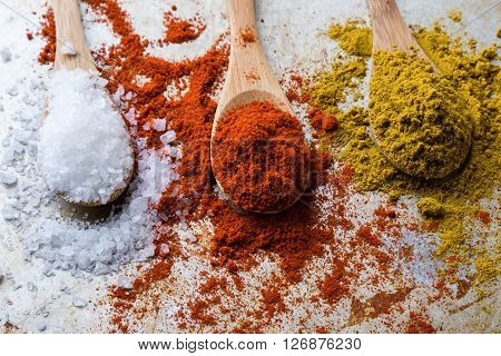 Salt, Paprika And Curry On Wooden Spoons