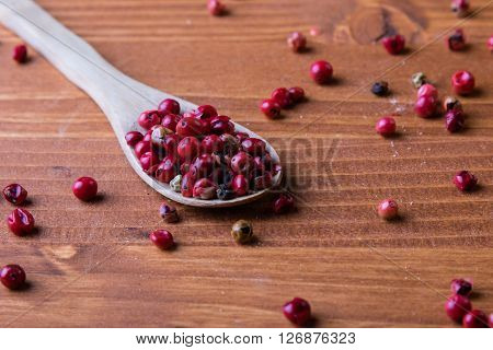 Red Peppercorn Seeds On Wooden Table