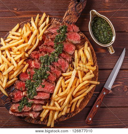 Beef barbecue ribeye steak with chimichurri sauce and french fries top view.