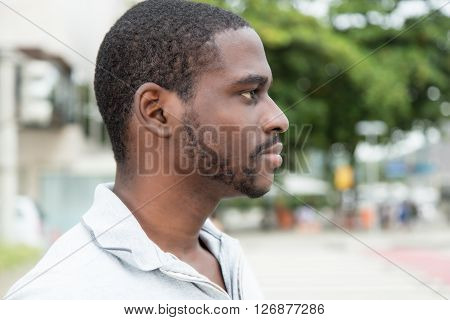 African man with beard looking sideways outdoor in the city