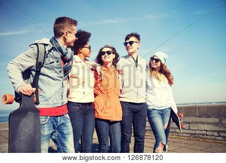 people, leisure and sport concept - group of happy teenage friends with longboards talking on city street