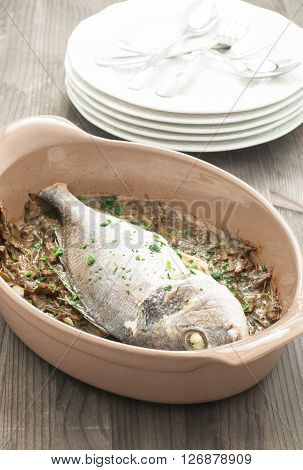 Fish cooked bream baked with stewed artichokes italy