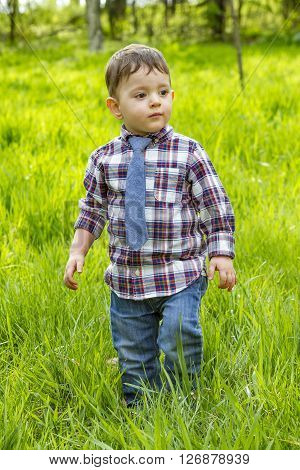 Little boy in shirt and jeans and striped tie walking in the grass in park.