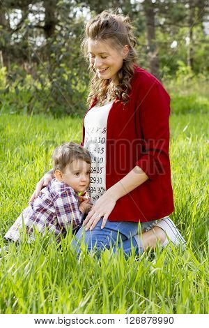 Beautiful pregnant woman outdoor with her little boy in thr park