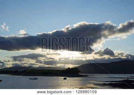 boats in a quiet bay with island near kenmare on the wild atlantic way ireland just before sunset