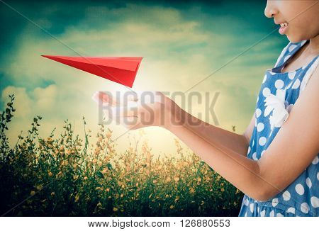 Little girl taking care a red aircraft paper origami is floating in her hands with flower field and cloudy blue sky