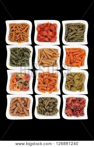 Coloured italian pasta selection in china dishes over black background with spinach, carrot, tomato and durum wheat colouring.