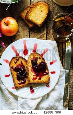Toast with jam and cup of tea on old wooden table. Delicious toast with jam on table close-up. Fresh cherry jam with toast for breakfast on rustic wooden background. Sweet cherry jam on toast.