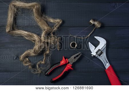Adjustable wrench pliers and fitting on wooden background.