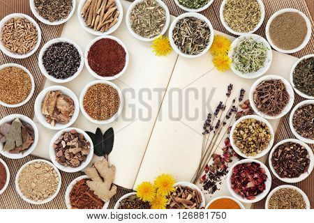 Herbal medicine selection used for womans health on natural hemp notebook over bamboo background.