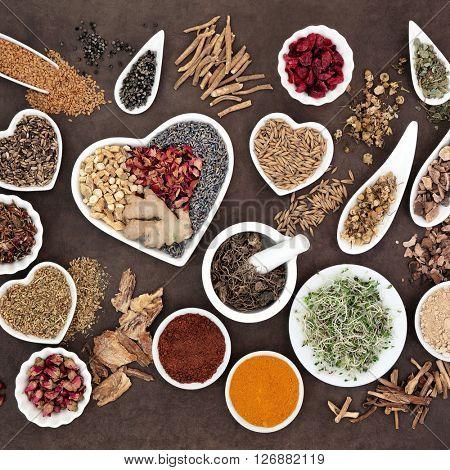 Herb selection used in female alternative herbal medicine over lokta paper background.