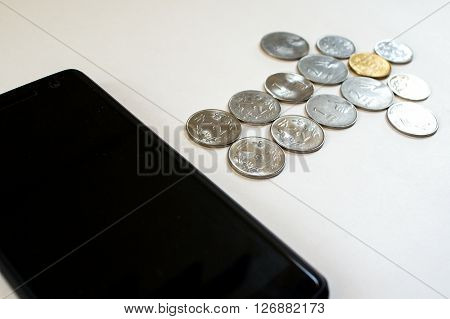 Arrow of coins flowing from mobile. Mobile phone with indian currency set on a white background. Denoting payment through mobile and mobile wallets