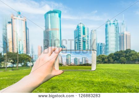 Human taking photo of city by smartphone,shanghai china
