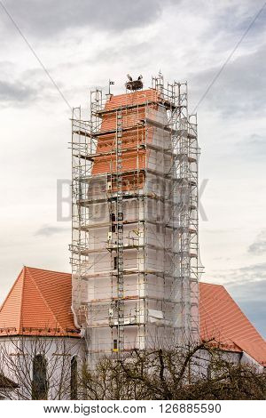 two storks in their nest above a scaffolded church spire