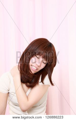 portrait of young Japanese woman suffers from neck ache