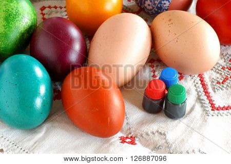 many various colorful easter eggs with liquid paint bottles