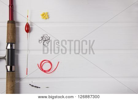 fishing gear on white rustic wood background