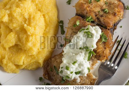 Delicious plate of fresh fried carp with polenta and garlic sauce