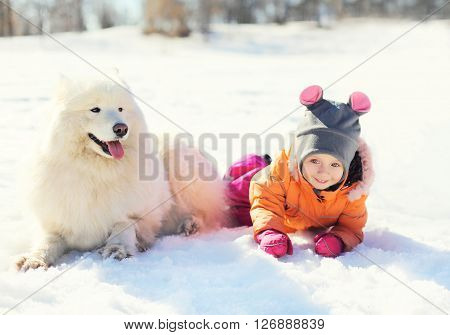 Child With White Samoyed Dog Lying On Snow In Winter Day
