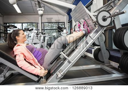 Pregnant woman using weight machine at the gym