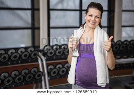 Smiling pregnant woman showing thumb up at the gym