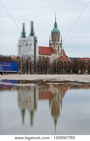 Munich Germany - January 08 2016: The towers of Saint Paul church in the reconstruction with reflection in water view from a meadow of Therese
