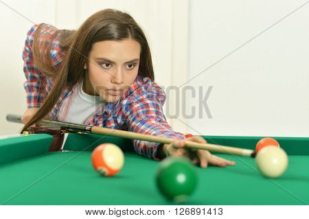 Portrait of a young girl with cue playing billiard
