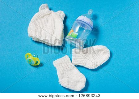 Knitted by hands wool white hat and socks for the newborn. Winter hand made clothing for the child on blue paper background. Hobbies for Women: knitting.