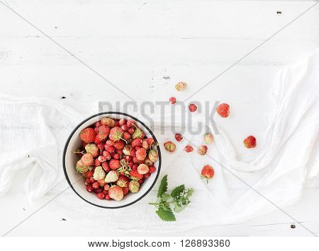 Wild strawberries in rustic metal bowl on white wooden background, top view, copy space