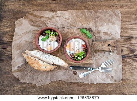 Country style breakfast set. Eggs baked in separate clay cups with tomatoes, peppers, fresh basil, bread slices on rustic board over oily craft paper and wooden background, top view, horizontal