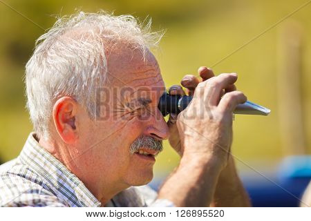 Viticulturist analyzing grape sugar level with refractometer