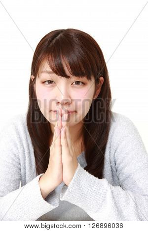 studio shot of woman folding her hands in prayer on white background