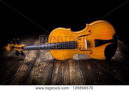 Single yellow violin on dark wooden background