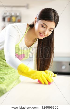 Beautiful woman in protective gloves cleaning kitchen table with sponge
