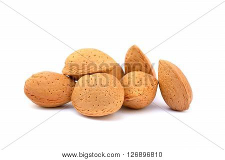 Pile of unpeeled almonds isolated on white background